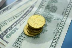 Zerstreute Banknoten von 100 US-Dollars und von Euromünzen Stockfotografie