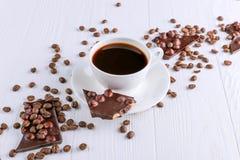 Zerstreute Kaffeebohnen, eine Schale und schwarze Schokolade auf einem wei?en Holztisch Kopieren Sie Platz lizenzfreie stockfotos