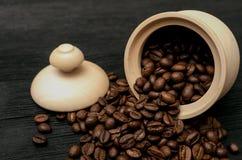 Zerstreute Kaffeebohnen von einem hölzernen Topf stockbilder