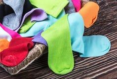 Zerstreute mehrfarbige Socken und Wäschekorb Lizenzfreie Stockfotografie