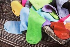 Zerstreute mehrfarbige Socken und Wäschekorb Lizenzfreies Stockbild