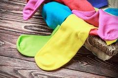 Zerstreute mehrfarbige Socken und Wäschekorb Stockfoto