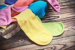 Zerstreute mehrfarbige Socken und Wäschekorb Lizenzfreies Stockfoto