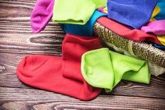 Zerstreute mehrfarbige Socken und Wäschekorb Stockbilder