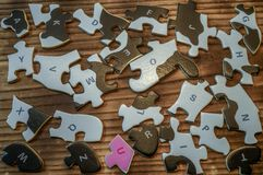 Zerstreute Puzzlespiele auf einem Holztisch lizenzfreie stockbilder