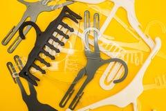 Zerstreute weiße und graue Aufhänger auf gelbem Hintergrund stockfoto