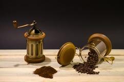 Zerstreuter gemahlener Kaffee der Kaffeebohnen und manuelle Kaffeemühle auf den hölzernen Brettern und auf schwarzem Hintergrund Stockfoto