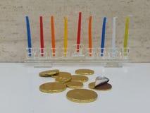 Zerstreutes chocholate prägt mit einem Glas-hannukiah, das mit bunten Kerzen im Hintergrund gefüllt wird Lizenzfreie Stockfotos