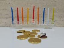 Zerstreutes chocholate prägt mit einem Glas-hannukiah, das mit bunten Kerzen im Hintergrund gefüllt wird Stockfoto