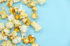 Zerstreutes gesalzenes Popcorn, Beschaffenheitshintergrund Popcornmuster auf blauem Hintergrund Beschneidungspfad eingeschlossen  lizenzfreie stockbilder