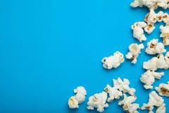 Zerstreutes Popcorn auf einem blauen Hintergrund Kopieren Sie Platz stockfotos