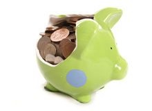 Zertrümmerte piggy Querneigung mit britischen Bargeldmünzen Lizenzfreies Stockfoto