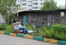 Zerzauste betrunkene Streufrau, die im Yard im antisozialen Verhaltenbesäufnis des Alkoholzustandsalkohols schädlich schläft stockfotografie