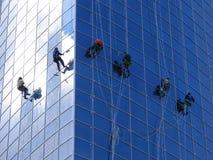 Zes arbeiders die vensters wassen stock foto
