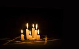 Zes brandende kaarsen en de Jodenster tegen een zwarte backgr Royalty-vrije Stock Afbeeldingen