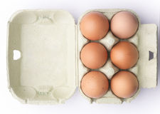Zes bruine eieren in een karton van hierboven geïsoleerd op wit Stock Fotografie