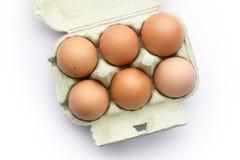 Zes bruine eieren in een karton van hierboven geïsoleerd op wit Royalty-vrije Stock Foto's