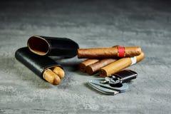 Zes Cubaanse sigaren op een steenlijst met een aansteker, snijder en een leergeval stock fotografie