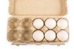 Zes eieren in een dienblad voor tien eieren isoleren Royalty-vrije Stock Afbeeldingen