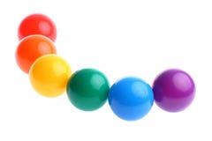 Zes glanzende gekleurde plastic stuk speelgoed ballen in rij Royalty-vrije Stock Foto's