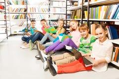 Zes glimlachende kinderen die op een rij op vloer zitten Stock Fotografie