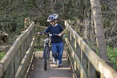Zes éénjarigenjongen die een fiets duwt Royalty-vrije Stock Fotografie