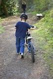Zes éénjarigenjongen die een fiets duwt Royalty-vrije Stock Foto's