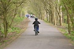 Zes éénjarigenjongen die zijn fiets berijdt Stock Foto
