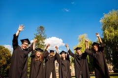 Zes opgewekte succesvolle gediplomeerden in zwarte robes en baret stock fotografie