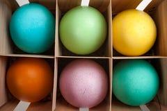 Zes pastelkleurpaaseieren in een printersdoos Stock Afbeeldingen