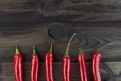 Zes Spaanse peperspeper op houten lijst Royalty-vrije Stock Fotografie