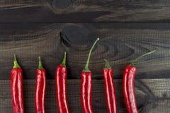 Zes Spaanse peperspeper op houten lijst Hoogste mening Royalty-vrije Stock Foto's
