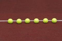 Zes tennisballen in-line op hof Royalty-vrije Stock Foto