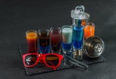Zes verschillende gekleurde geschotene die dranken, op een zwarte steenpla worden opgesteld Royalty-vrije Stock Afbeelding