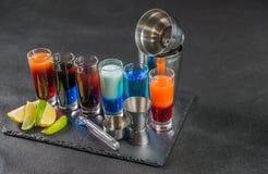 Zes verschillende gekleurde geschotene die dranken, op een zwarte steenpla worden opgesteld Stock Afbeelding