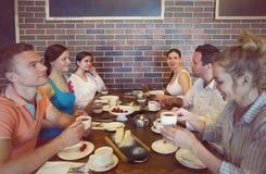 Zes vrolijke vrienden die terwijl lunch in restaurant babbelen royalty-vrije stock fotografie