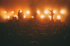 Zespół rockowy na scenie w backlights przed tłumem obrazy stock