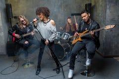 Zespół rockowy próbuje w muzykalnym studiu, zespół na sceny pojęciu Obrazy Royalty Free