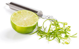 Zest of lime. Half of lime fruit; zest and zester on white Stock Photo