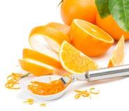 Zest of orange. Zest in white bowl, orange fruits and zester,    on white background Royalty Free Stock Photography