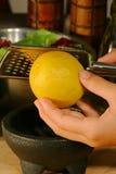 Zesting a lemon. For salad dressing Stock Photo