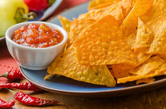 Zesty Cheese Nachos. A plate of zesty cheese nachos with spicy salsa and peppers stock photos