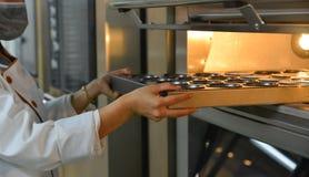 Zet cakes in de oven bij bakkerij stock afbeeldingen