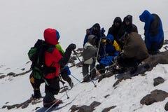 2014 zet Elbrus, Rusland op: het beklimmen tot de bovenkant met een gehandicapte persoon Stock Foto