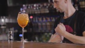 Zet het barman gietende water van plastic fles in hoog cocktailglas met ijs en plak van sinaasappel binnen dichte omhooggaand jon stock videobeelden