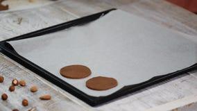 Zet ruwe chocoladekoekjes op een bakseldienblad met perkamentdocument, klaar voor bak stock videobeelden