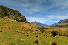 Zet Zondag en omringende die bergketens op, in filmlord wordt gebruikt van de scène van Edoras van de Ringenfilm, in Nieuw Zeelan Stock Foto