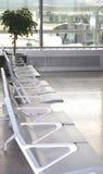 Zetels tegengesteld aan groot venster van luchthaven stock fotografie