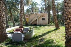 Zetels voor een kleihuis in een groene oase stock afbeeldingen