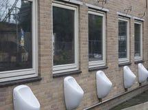 Zetten Mensen` s openbare pissoirs op een muur in centrum van Amsterdam op, stock afbeeldingen